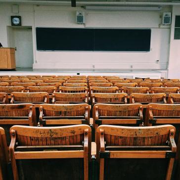 Bild eines leeren Hörsaals mit Blick über Stuhlreihen aus Holz in Richtung einer breiten dunkelgrünen Tafel