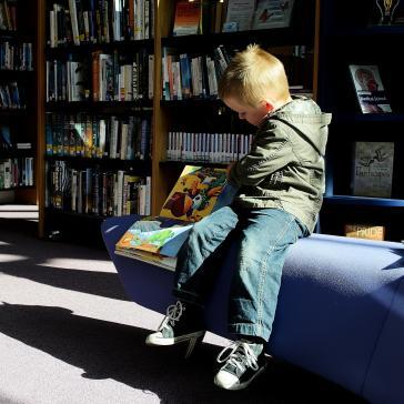 Bild eines Jungen vor Bücherregalen, der sich ein aufgeschlagenes Buch ansieht
