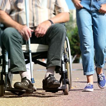 Rollstuhl, darin ein älterer Herr mit Pflegerin