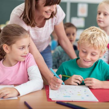 Ein Mädchen und ein Junge sitzen in der Klasse einer Grundschule an ihren Aufgaben. Eine Lehrerin hilft.